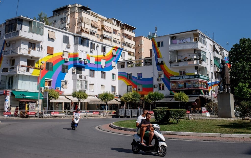 A white building in Tirana covered with a swirly rainbow.