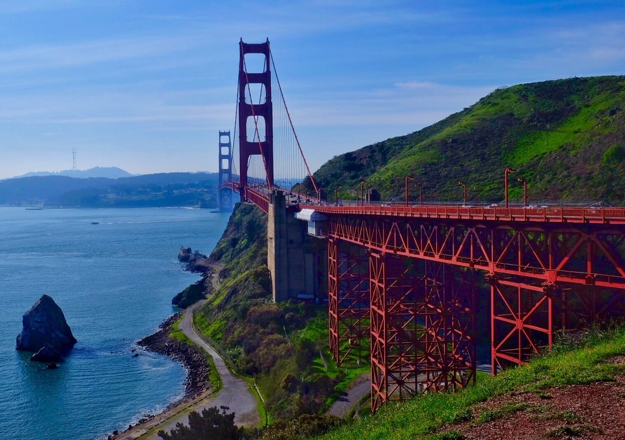 The Golden Gate Bridge rises up from the Sausalito side. It's bright red and extends into the distance, set against green cliffs, above a bright blue ocean, and underneath a streaky blue and white sky. San Francisco is misty in the background.