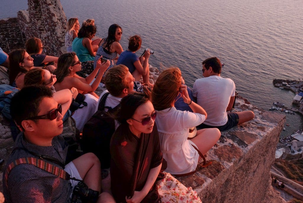People lit with red light, sitting on a ledge in Santorini, waiting for sunset.