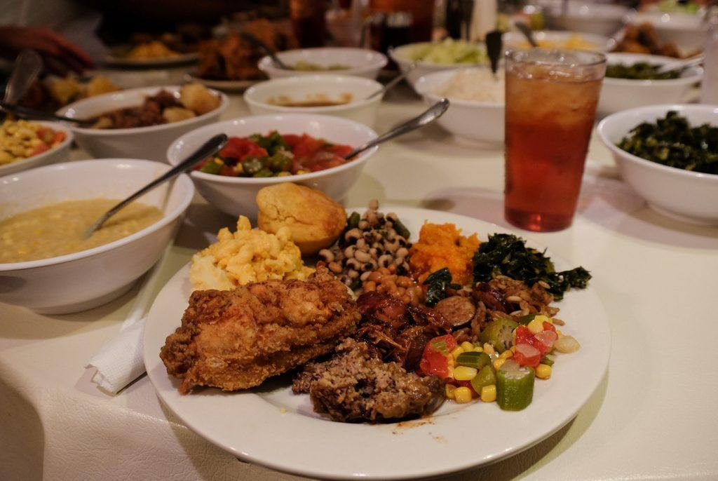 A plateful of food -- fried chicken, cornbread, black eyed peas, squash, and more -- with family-style plates in the background at Mrs. Wilkes' Dining Room in Savannah.