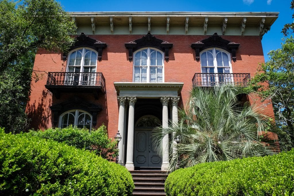 The Mercer House in Savannah: a red brick house with two white columns on each side of the entrance, lots of plants and vegetation in front.