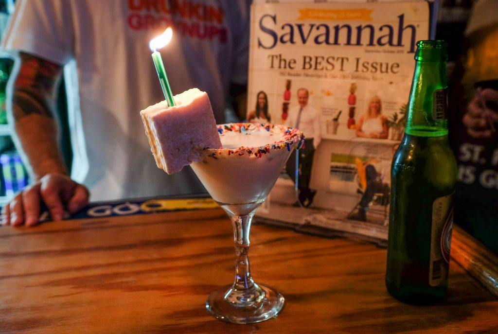 A martini glass with a white liquid inside, rainbow sprinkles on the edge, with a white hostess cake on the rim, a lit green birthday candle sticking out of it.