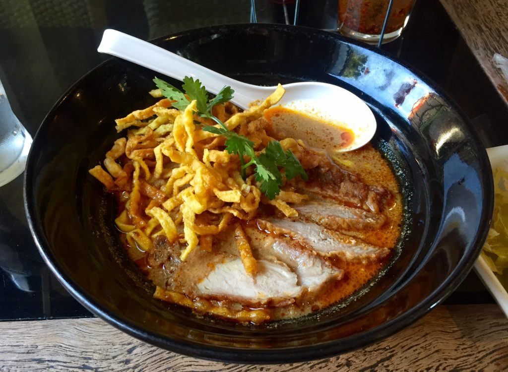 A bowl of Khao soi noodle soup topped with wontons in Chiang Mai.