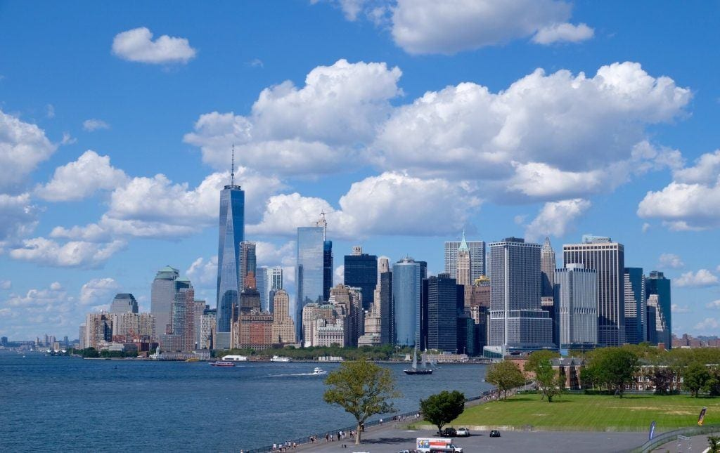The Manhattan skyline underneath a partly cloudy sky, buildings rising up in shades of blue and gray.