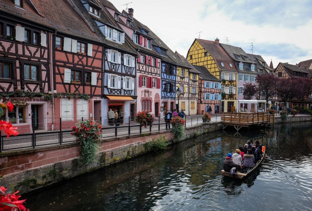 A canal in the city of Colmar, France, with multicolored half-timbered homes along the water. A small boat with people in it floats in the water.