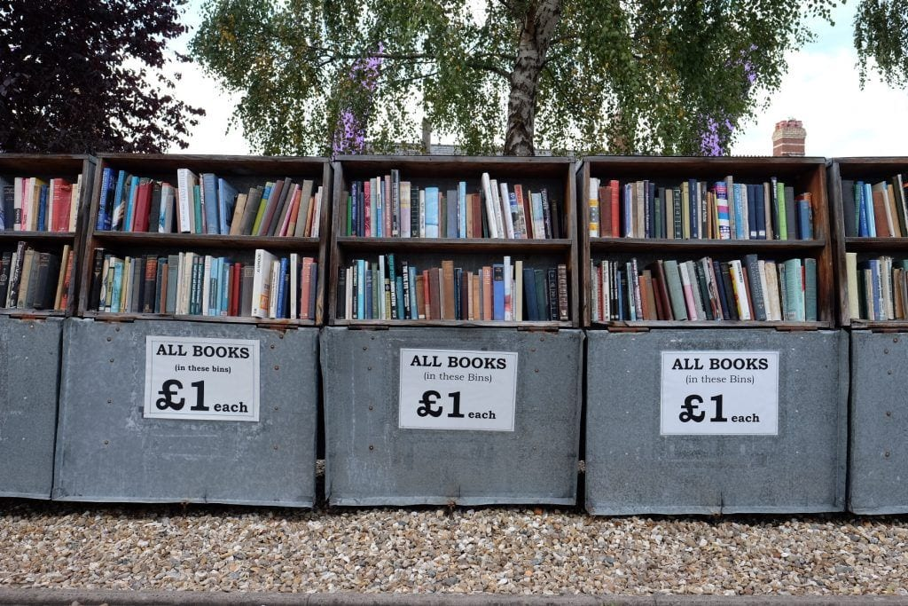 """Rows of used books for sale with a sign labeled """"all books 1 pound"""" in Haye on Wye, Wales."""