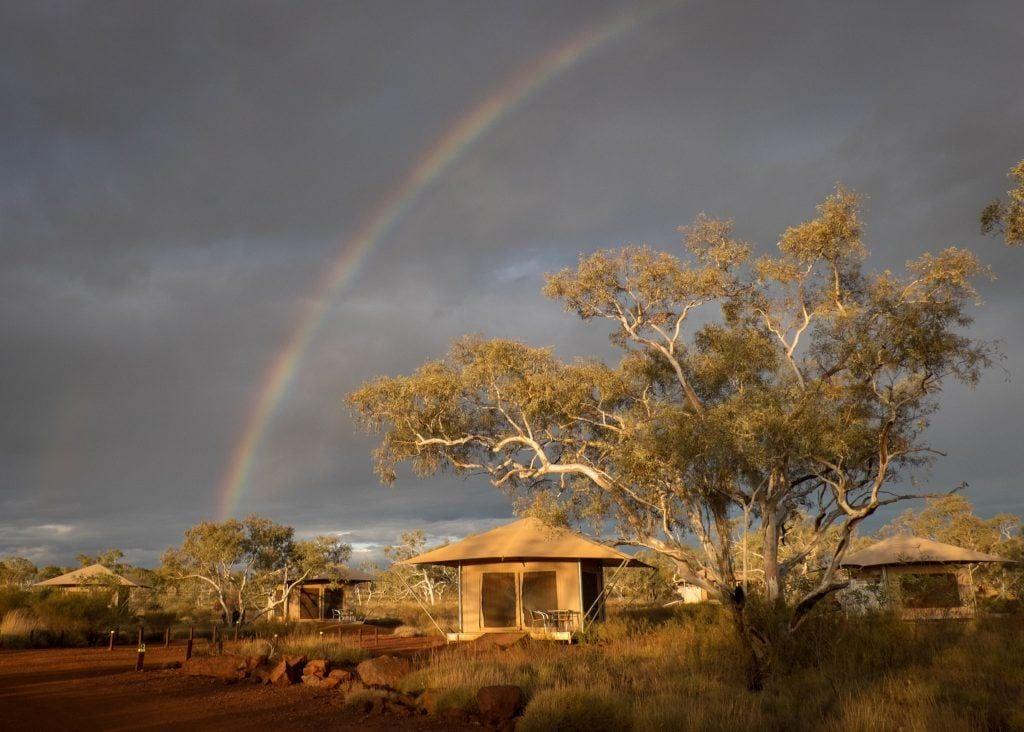 A rainbow over a tent in Karijini National Park, Australia
