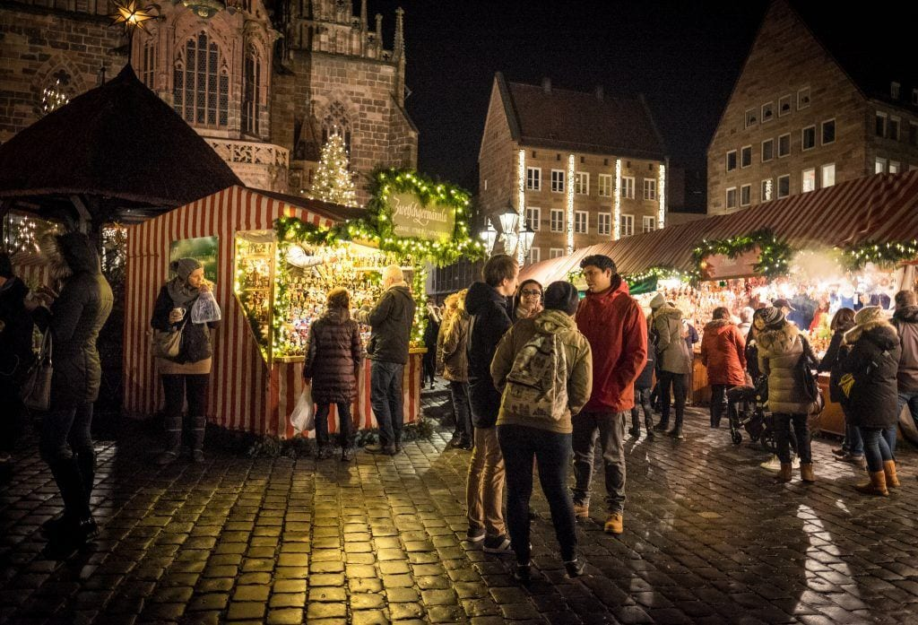 People gathered on a cobblestone square at Nuremberg Christmas Markets, surrounded by booths selling Christmas crafts.