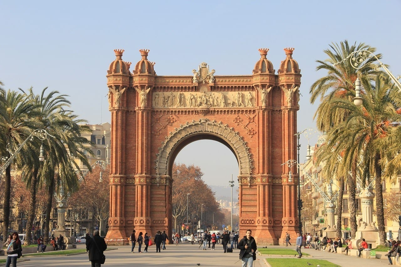 "Barcelona's red-colored ""Arc de Triomf, tall palm trees on each side of it."