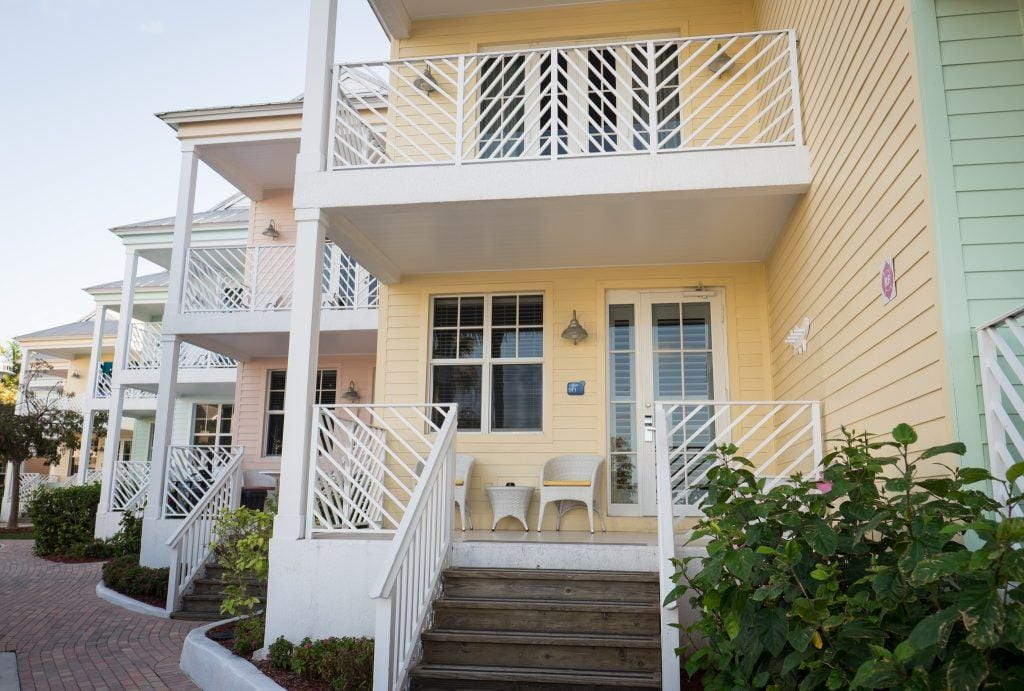 A butter-yellow cottage with white trim and a porch in Islamorada, Florida Keys.