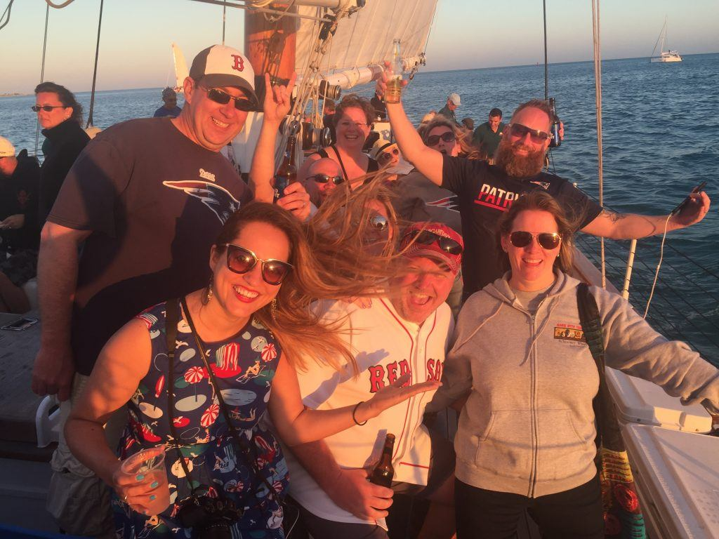 Kate and a group of 50-something folks, most of them wearing Boston sports gear, grinning in the sun on a sunset booze cruise