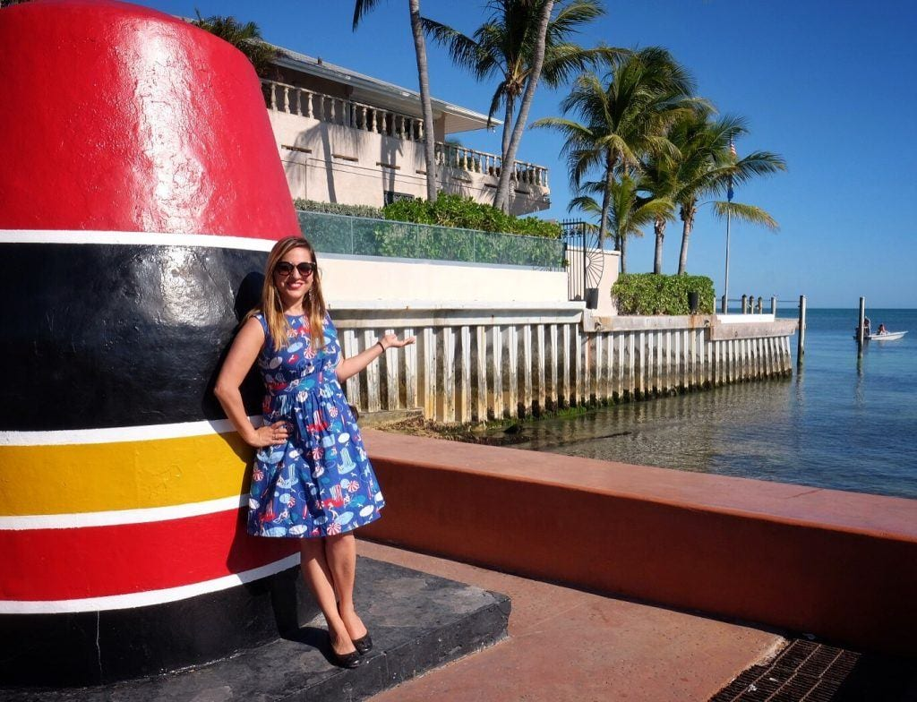 Kate wears a bright blue knee-length 50s housewife style dress and has long blonde straight hair, standing in front of the red, black, and yellow stone monument marking the southernmost point in the continental United States.