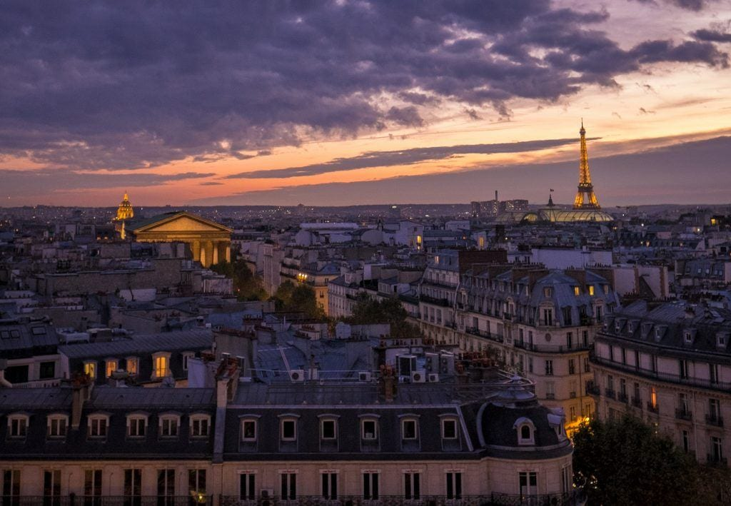A purple cloudy sunset in Paris. You see the rooftops in the fading light and on the right, in the distance, the Eiffel Tower lit up in orange.