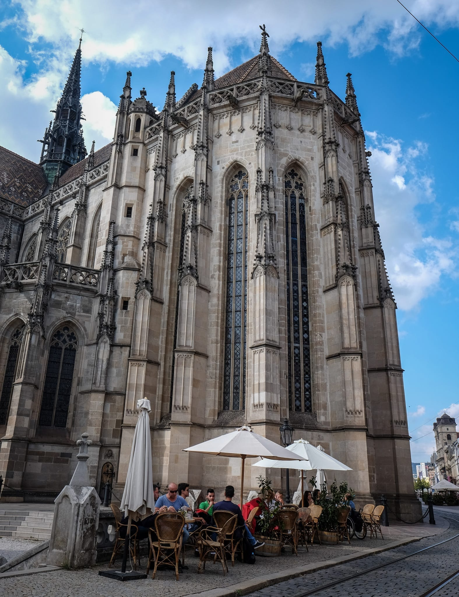 A city where locals sip beers at the base of a cathedral. 77b376f3e3b