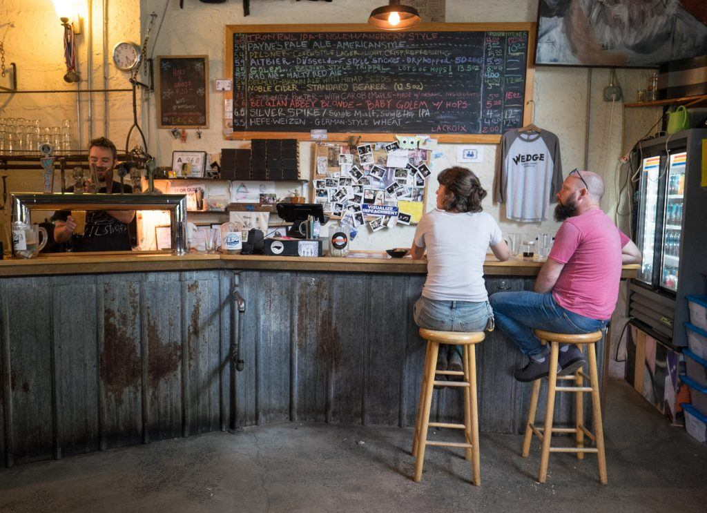 A man and a woman sitting on bar stools at an industrial-looking brewery in Asheville, North Carolina.