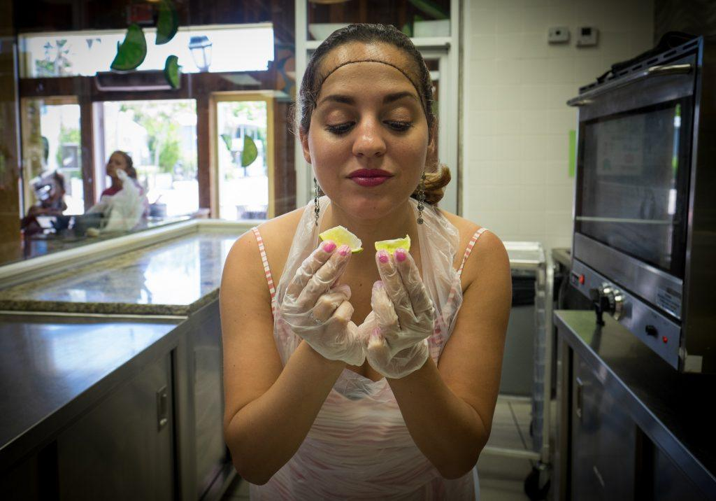 Kate in a kitchen, wearing a hair net and plastic gloves, holding two tiny key lime slices.