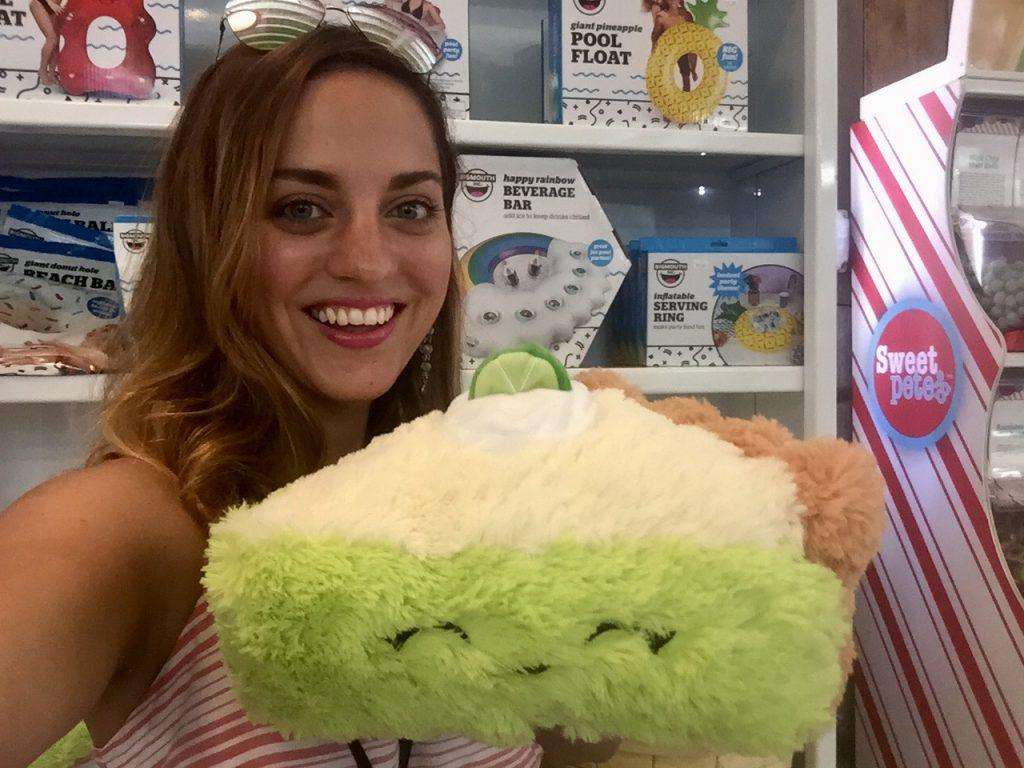 Kate holds a plush stuffed animal of a slice of key lime with a smile on its face.