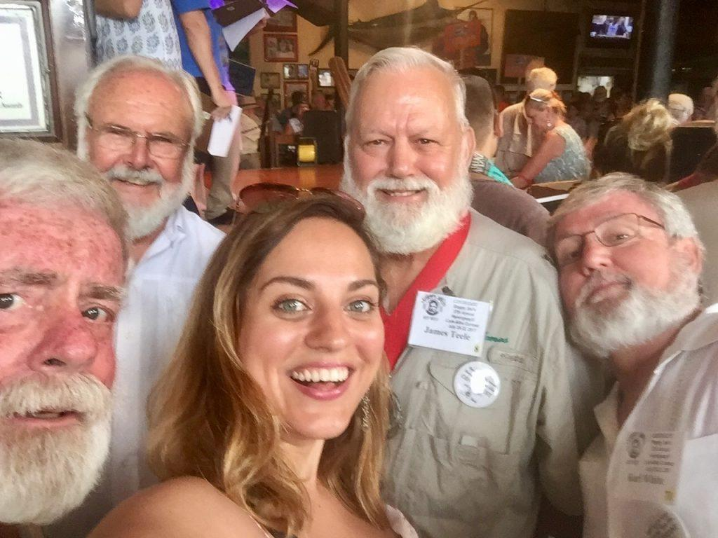 Kate taking a selfie with four Hemingway lookalikes in Key West, all with big white beards and wearing khaki shirts.