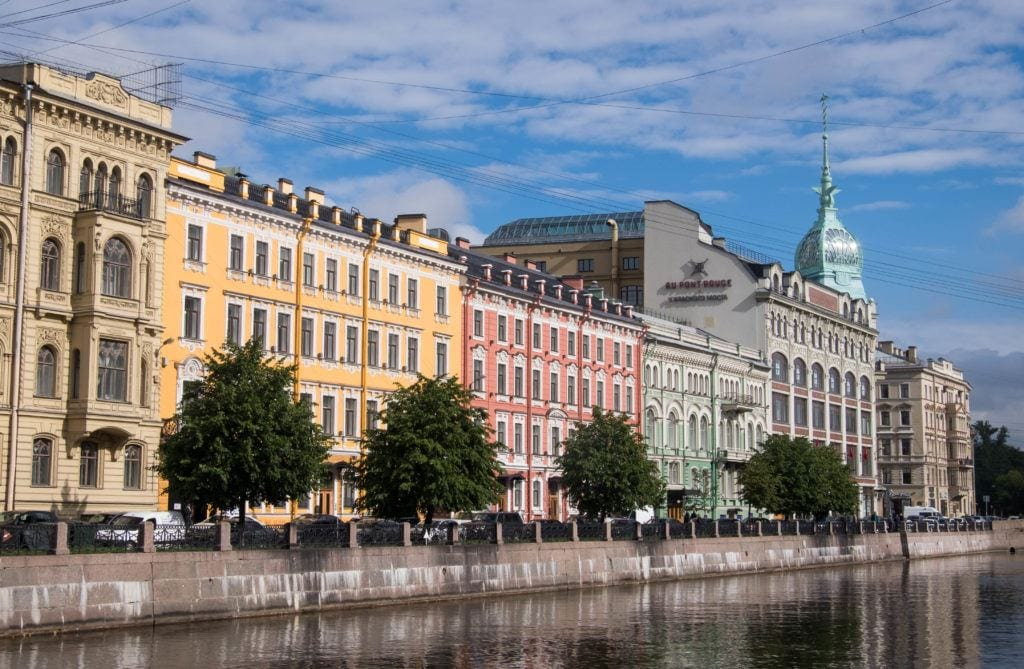 Buildings in St. Petersburg along the river, in the colors of yellow, salmon pik, and mint green.