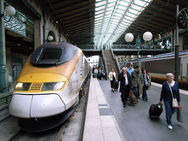 Taking a trip from London to Paris by train, a yellow train prepares to leave the station.