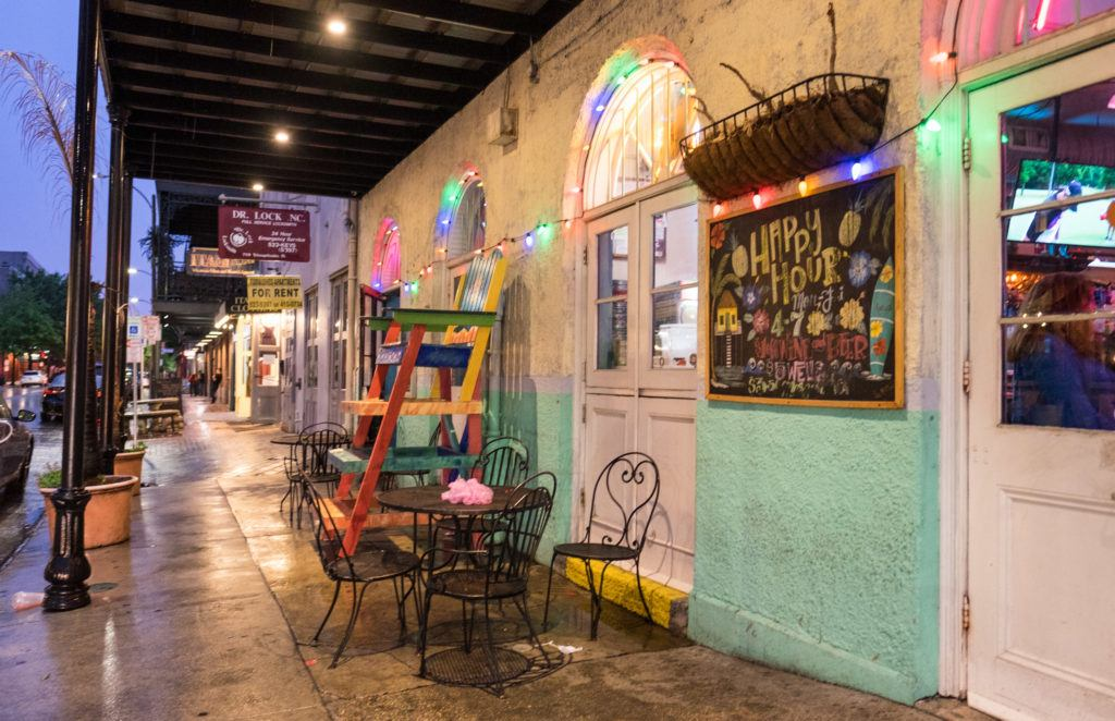 A New Orleans cafe on the street at night, colored lights dangling outside, people sitting on wrought iron chairs and enjoying cocktails.