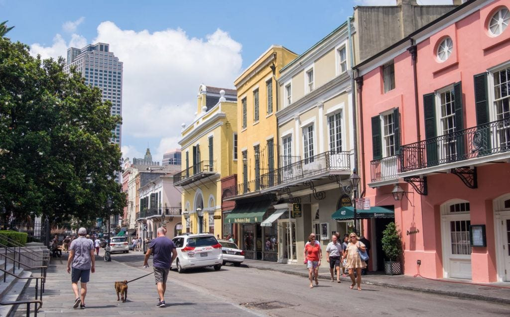 Two women walking a dog down the street in the French Quarter of New Orleans, the street lined with three-story buildings with balconies, the houses painted pink, yellow, and white.