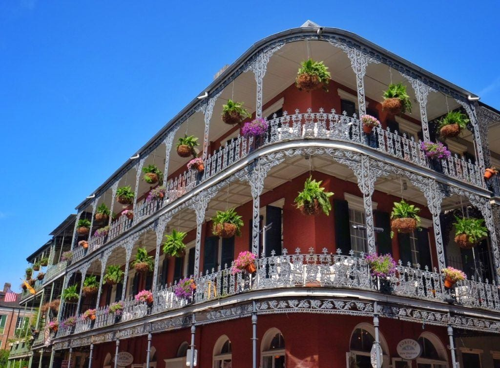 A building in the French Corner of New Orleans: it's orange with three floors, all edged with porches and black wrought0iron balconies. Big bunches of flowers dangle from each balcony.