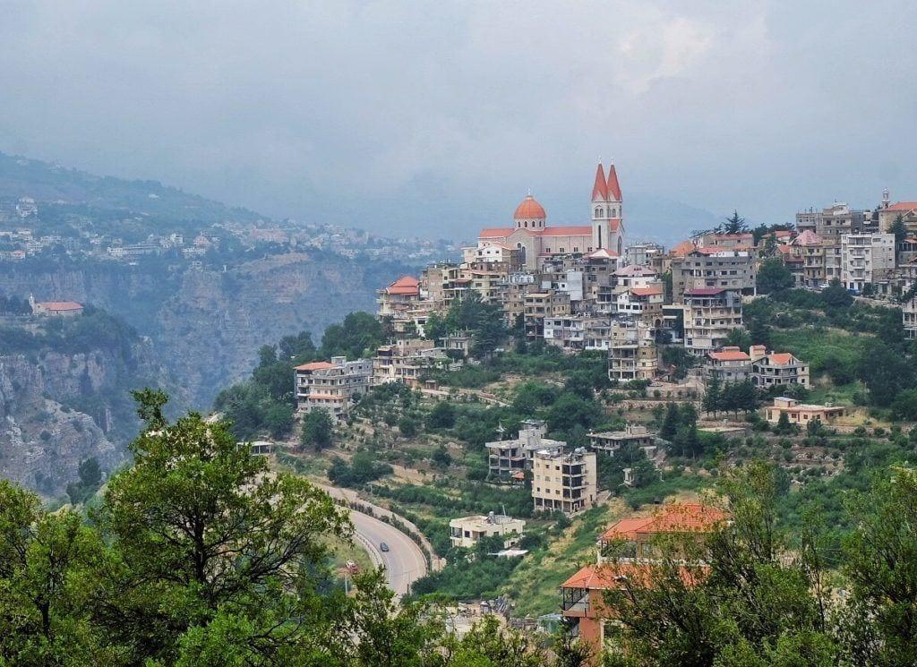 La ciudad de Bcharre, Líbano, en la distancia: ves una pequeña ciudad de piedra blanca y techos anaranjados encaramada en una colina empinada, vegetación asomando entre los edificios, una torre de iglesia asomando en la parte superior.  Es un día de mal humor con espesas nubes grises.