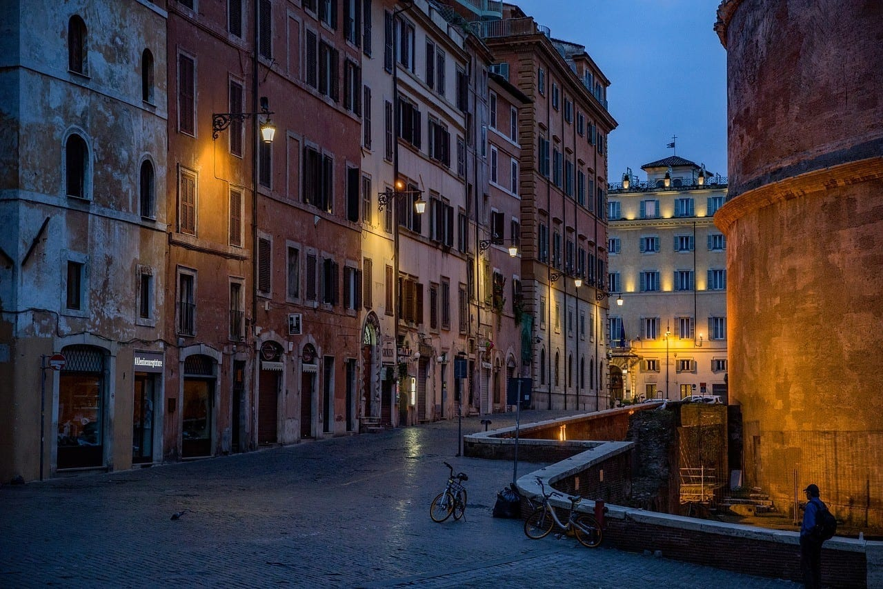A small alleyway in Rome at dusk, brightly colored buildings lit by yellow streetlamp.