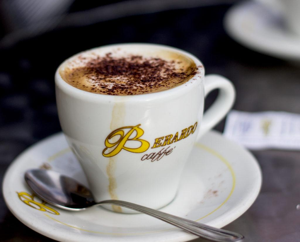 A white ceramic cup filled with espresso and milk, dusted with chocolate on top.