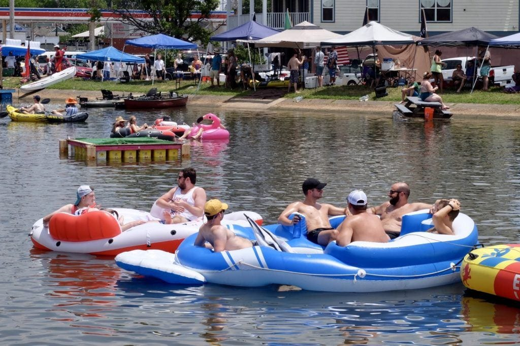 People in New Orleans sitting on giant floats in the middle of a city bayou (which looks more like an urban canal than a bayou).
