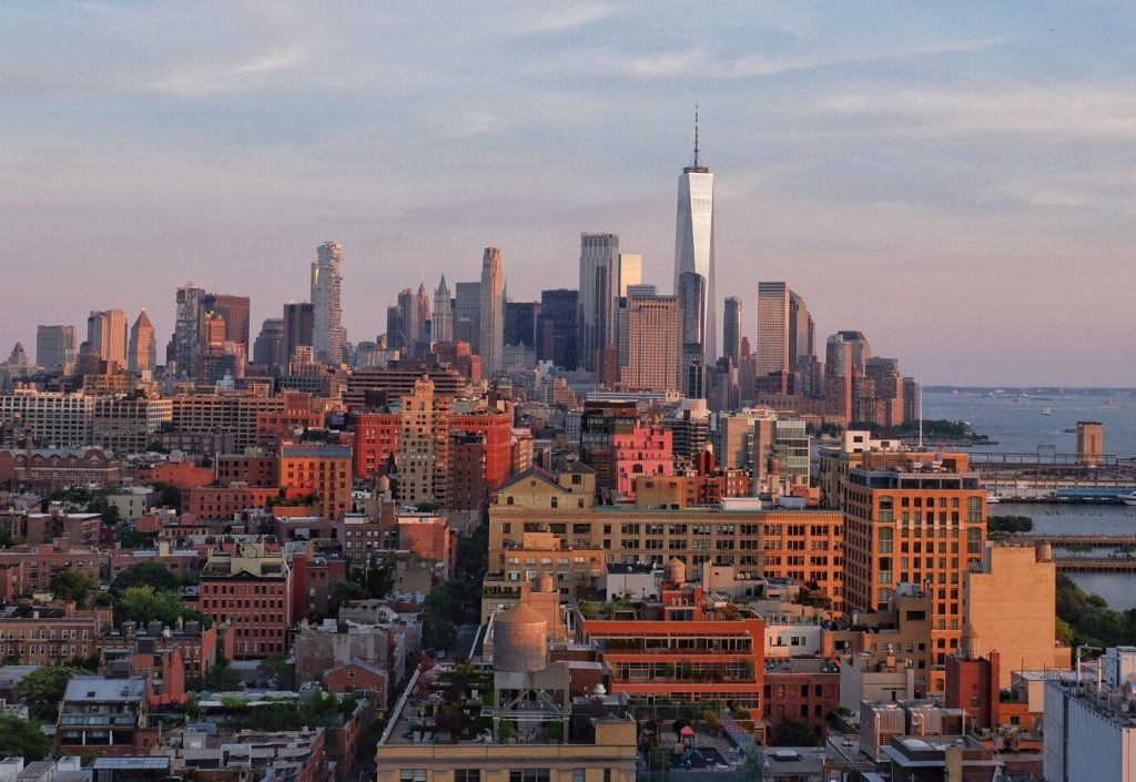 The New York skyline as seen from Hell's Kitchen, the buildings brown and silver underneath a blue and pink sunset.