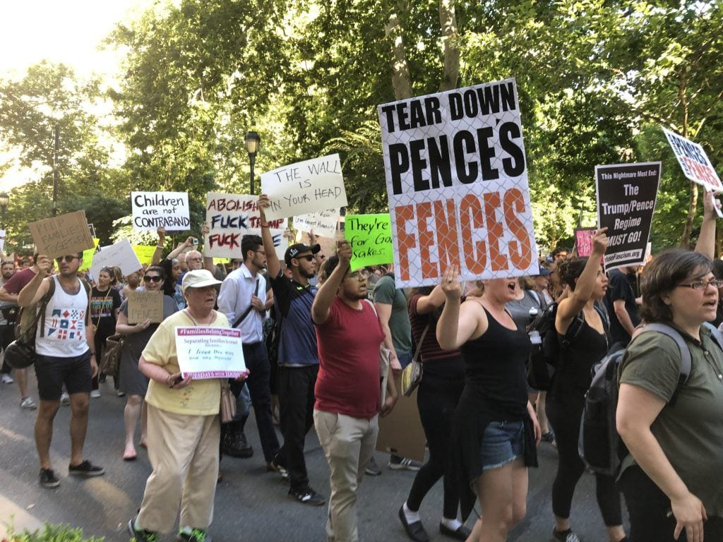 """Protestors in Philadelphia holding signs, one says """"Tear down Pence's Fences."""""""