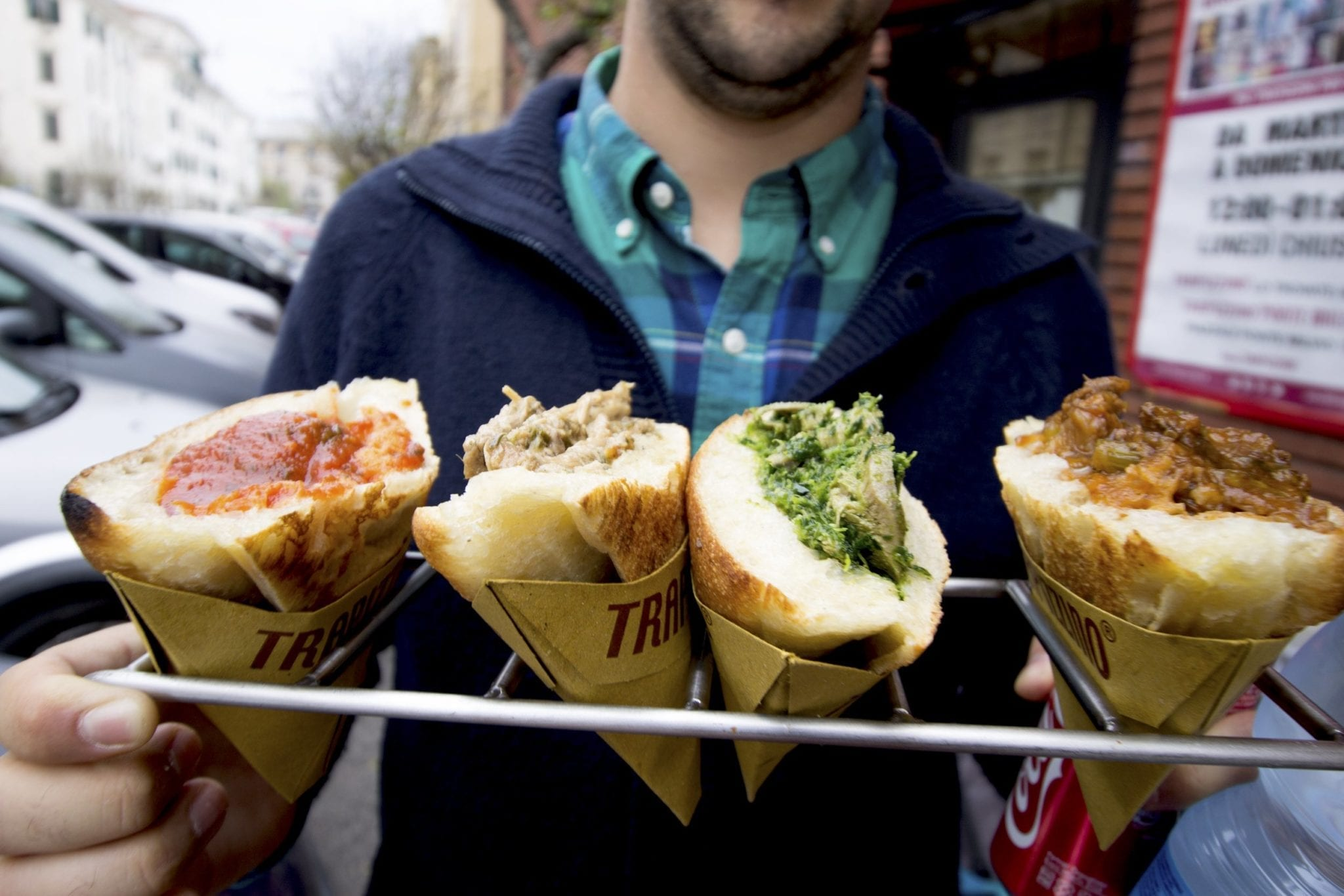 A man holds up four cones of what looks like bread topped with sauce in Rome.