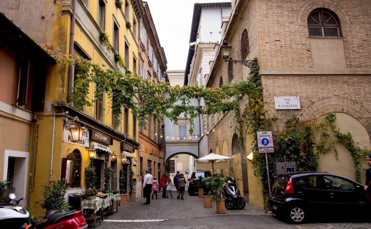A quiet side street in Trastevere, Rome, with yellow painted buildings and ivy-covered arches, fairy lights in the background.