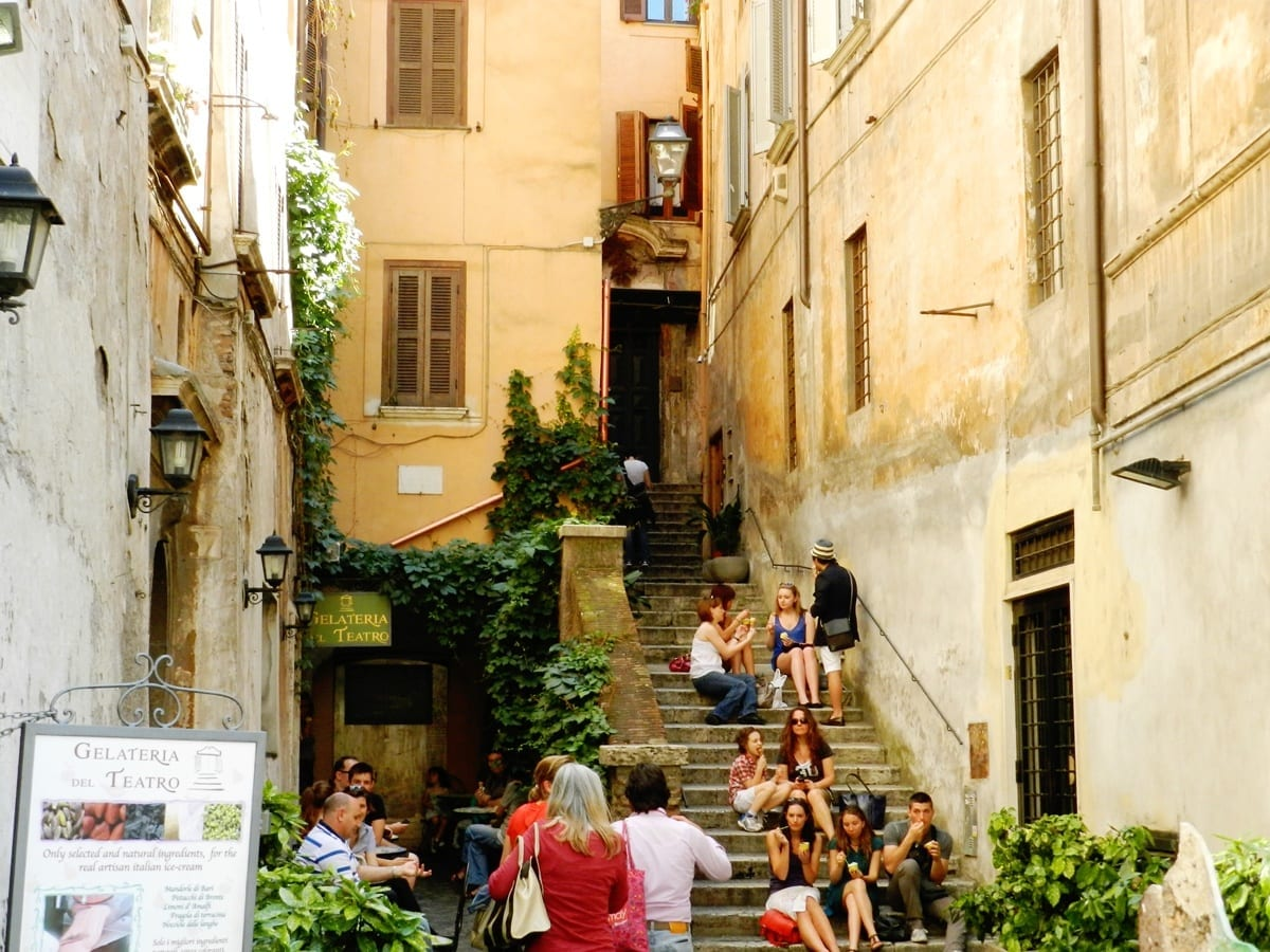 Groups and families sitting on a narrow staircase in Rome's Centro Storico.
