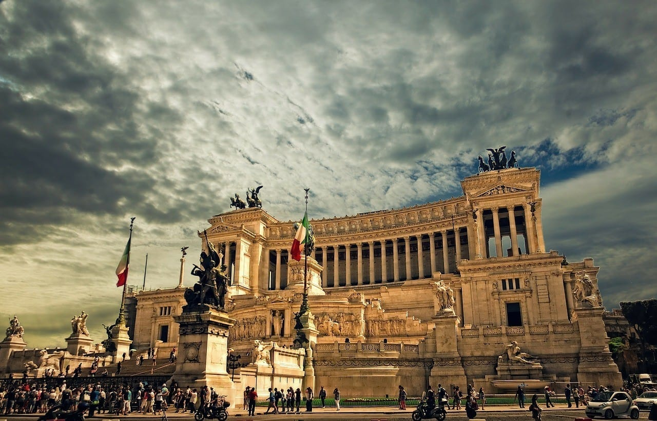"Vittorio Emanuele, the ""wedding cake"" building of Rome with large columns and Italian flags flying, bright yellow at dusk beneath a cloudy sky."