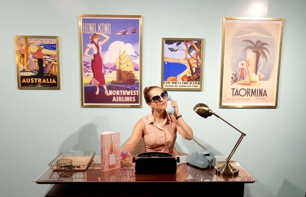 Kate wearing sunglasses and sitting behind a desk, on the phone, with vintage travel posters behind her.