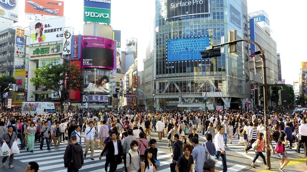 Hundreds of people cross the enormous Shibuya Crossing in Tokyo as tall buildings covered with screens and advertisements surround them.