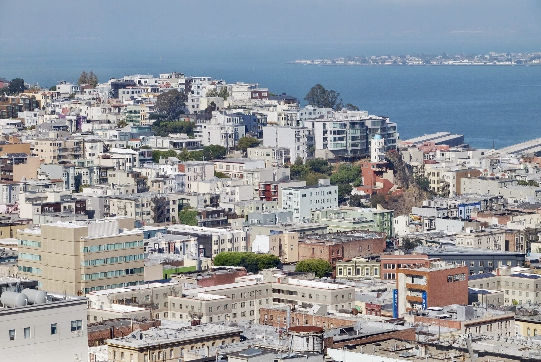 The San Francisco neighborhoods of Russian Hill and North Beach have square-shaped buildings stacked on top of each other, ascending and descending down the hills with occasional trees. In the background is San Francisco Bay and you can see Oakland through the haze in the distance.