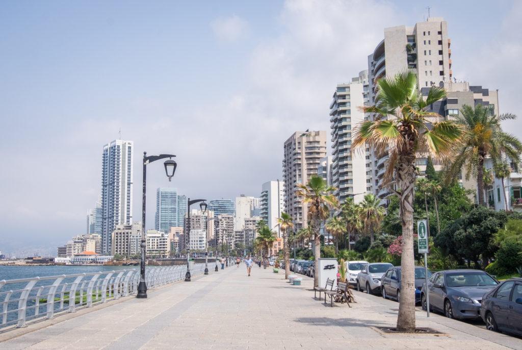 La cornisa en Beirut: un ancho camino de cemento a lo largo del mar.  Al fondo hay grandes rascacielos y palmeras.