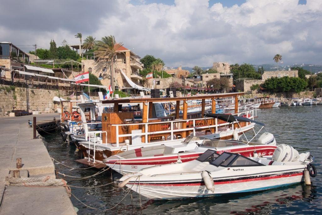 Una hilera de pequeños botes blancos atracados en el borde de un muelle de piedra, con la ciudad color arena de Byblos al fondo.