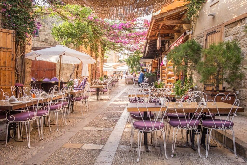 Un patio en Byblos, Líbano, con muchas mesas de madera con sillas blancas.  Hay sombrillas y muchas plantas.  Se siente como si estuvieras en medio de una habitación secreta de arena.
