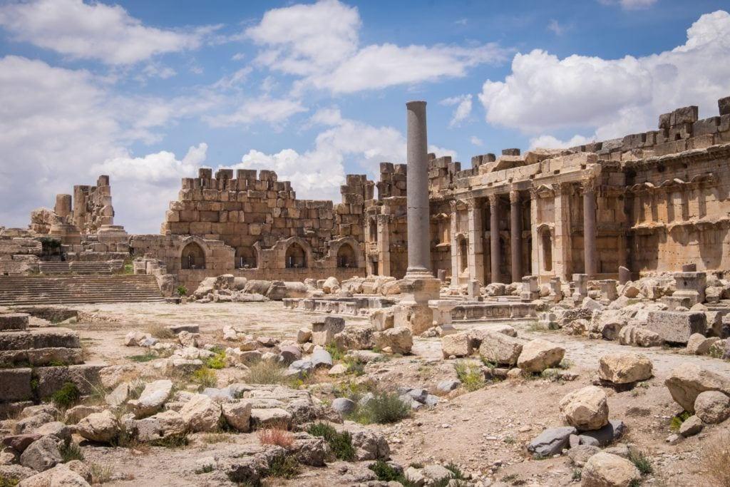 Las ruinas romanas de color arena de Baalbek parecen un paisaje bombardeado, todo de color marrón anaranjado debajo de un cielo parcialmente nublado.