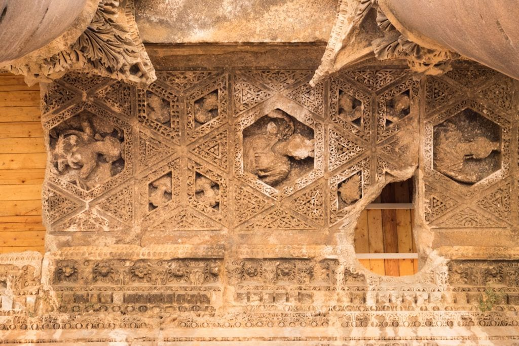El techo de uno de los templos de Baalbek: un intrincado patrón tallado en la piedra arenisca, algunas partes erosionadas, algunas de las partes faltantes reemplazadas por tablas de madera.