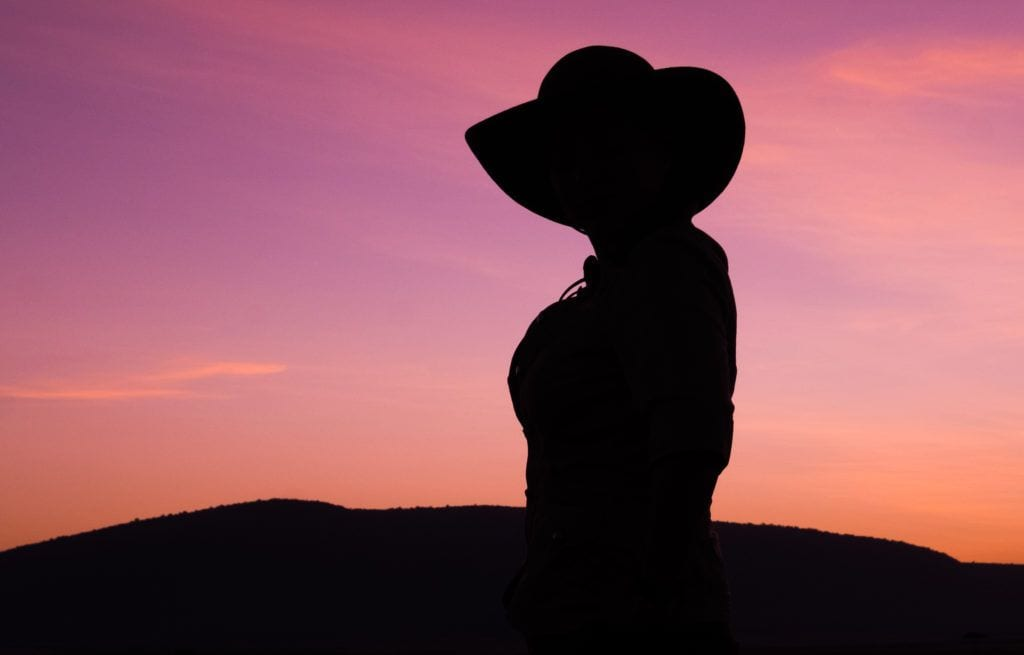 Kate silhouetted during a pink sunrise in Kenya, wearing a wide-brimmed hat.