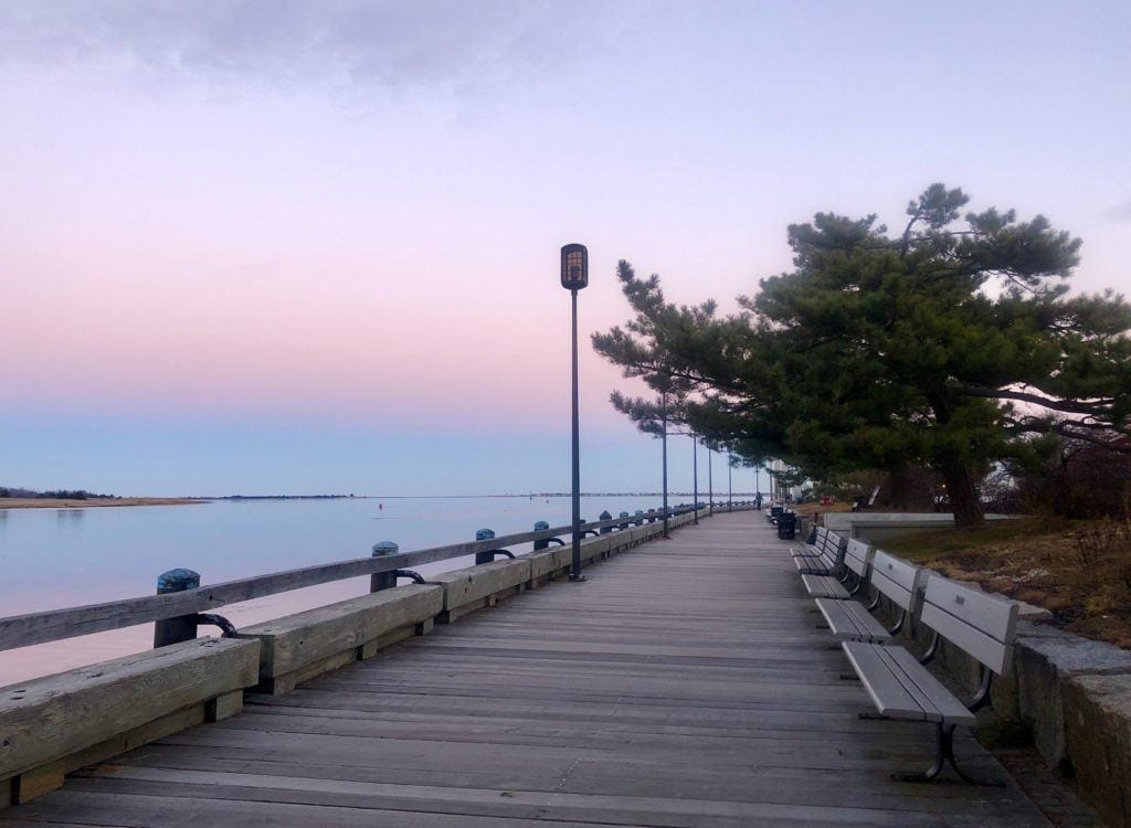 A wide wooden pathway along the water in Newburyport, Massachusetts, lined with benches. There is a pink and purple sunset and it reflects in the water.