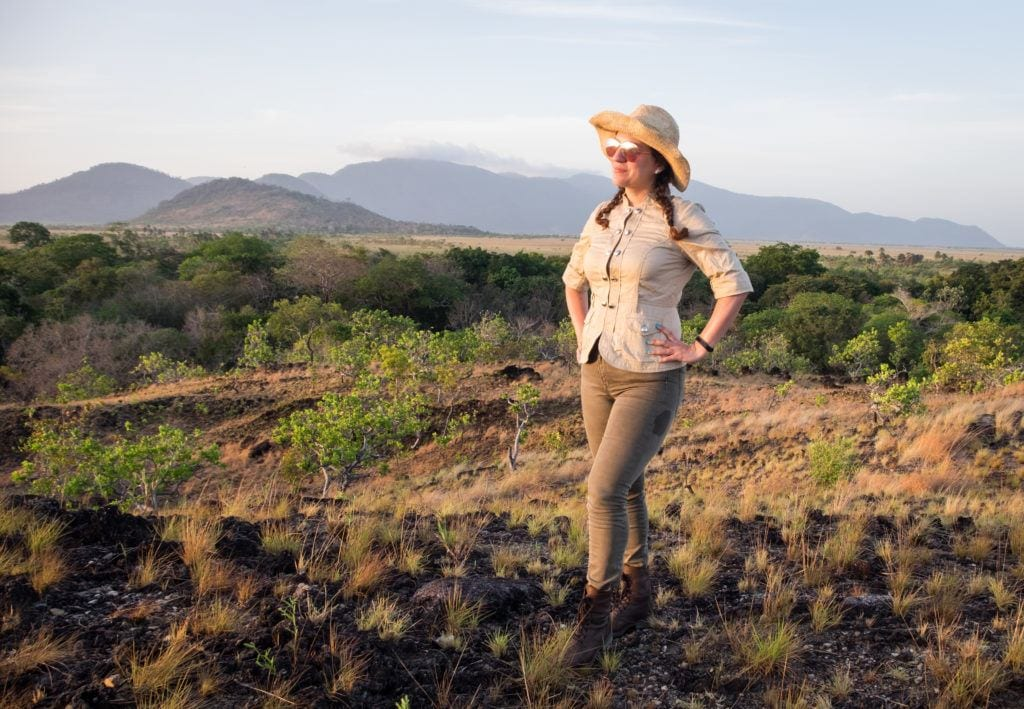 Kate wearing a tan jacket and green pants and boots, and a hat, looking out over the savannah grasslands in the Rupununi of Guyana.