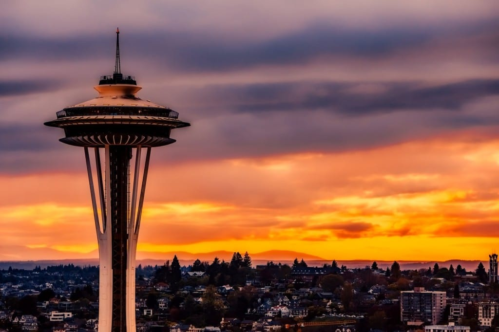 The Space Needle lit up with an orange and purple sunset behind it.