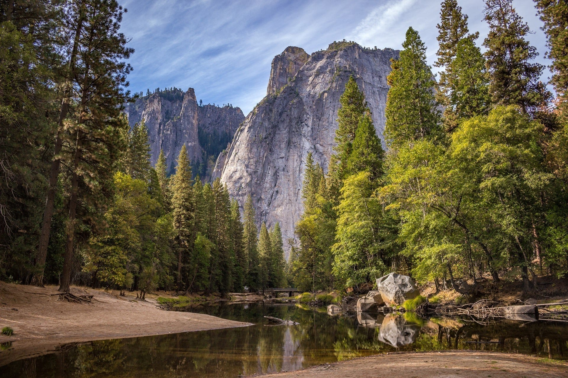 Yosemite National Park has huge looming mountains in the background underneath a blue and white streaky sky. There are bright green evergreen trees and water on the ground amongst the brown land.